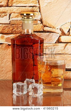 Bottle and Glass of whiskey and ice on brick wall background