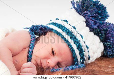 Newborn baby in knitted hat with pom-pons