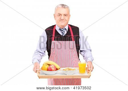 A smiling gentleman in apron carrying a tray with drinks and food isolated against white background