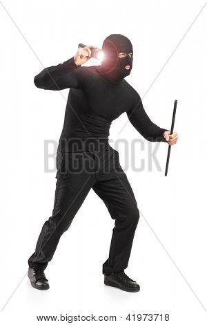 Full length portrait of a robber with robbery mask holding a flashlight and piece of pipe isolated on white background