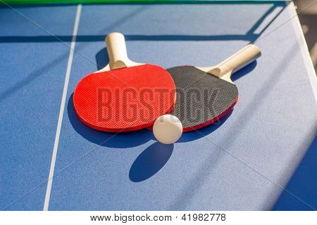 table tennis ping pong two paddles and white ball on blue board