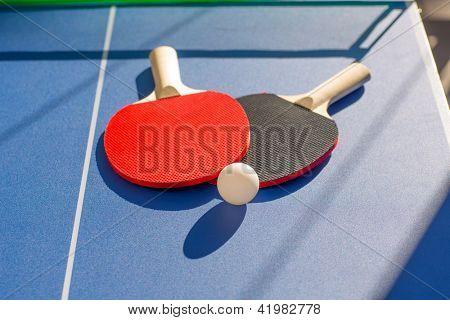 dos paletas de tenis de mesa ping pong y la bola blanca en blue board