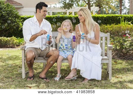 A young family mother & father parents with girl child blowing bubbles having fun together sitting on a bench in a sunny park or garden.