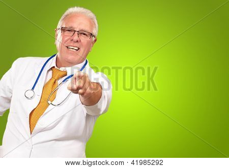 Portrait Of A Senior Doctor Pointing On Green Background