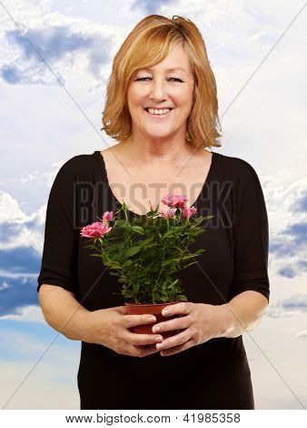 Woman holding flower pot, outdoor