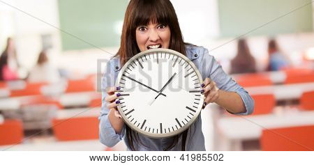 A Young Girl Holding A Clock And Angry, Indoor