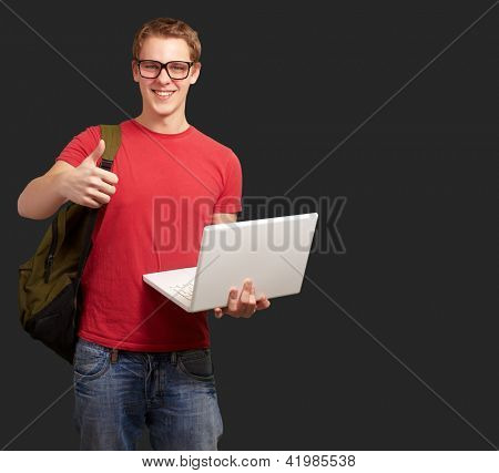 man holding laptop and backpack isolated on black background