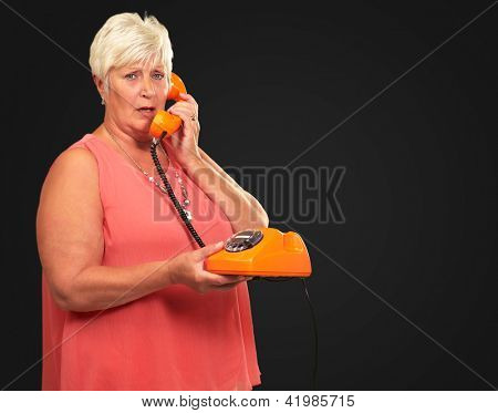 Portrait Of A Senior Woman Holding A Retro Phone On Black Background