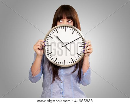 A Young Girl Holding A Clock On Gray Background