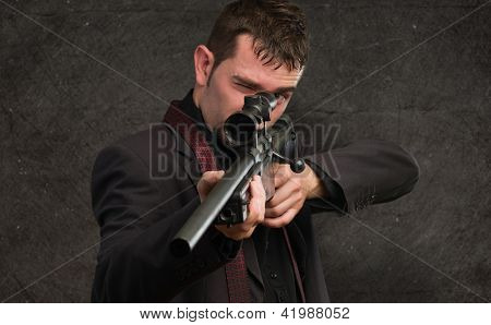 Man in suit pointing with a rifle against a grunge background