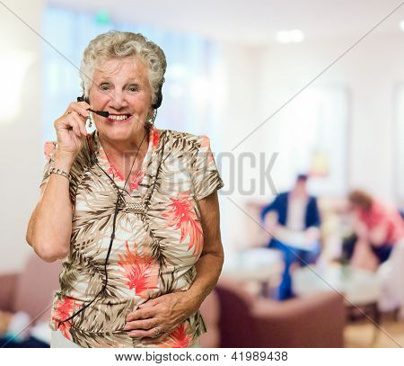 Portrait Of Cheerful Senior Woman With Telephone Headset, Indoors