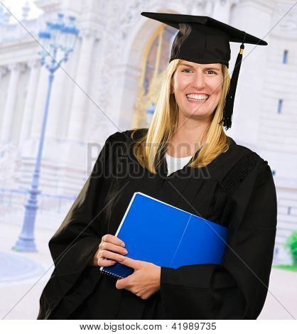 Happy Graduate Woman Holding a notebook in front of a building, outdoor