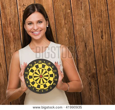 Portrait Of A Young Woman Holding Bull's Eye Smiling against a wooden background