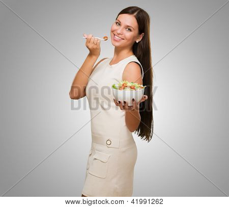 Portrait Of A Young Woman Holding A Salad against a grey background