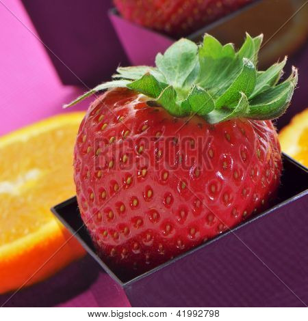strawberries and orange slices in cubical and round bowls