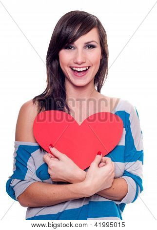 Pretty smiling girl holding a red heat isolated on white
