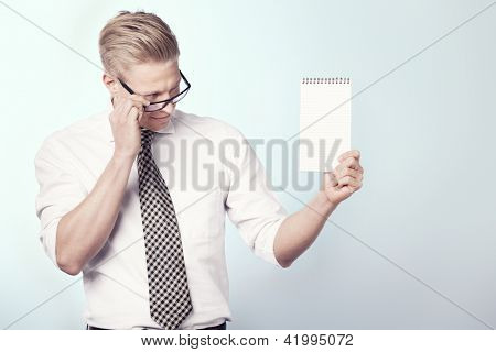 Smiling businessman looking at blank notepad with space for text while holding it, isolated.