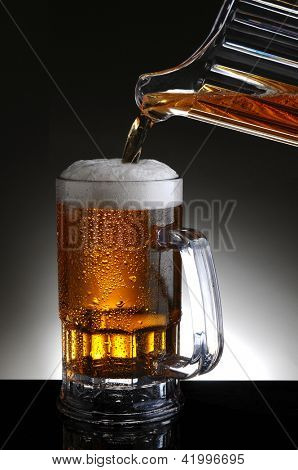 Closeup of a beer mug being filled from a pitcher pouring cold ale into the glass. Vertical format on a light to dark gray background.