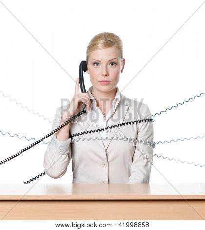 Young businesswoman sitting at a office desk tied with phone cord, isolated