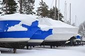 stock photo of tarp  - Boats in snow with bright blue shrink wrap - JPG