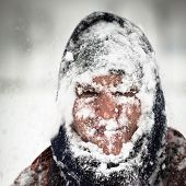 foto of windy weather  - Man covered by snow in heavy snowstorm - JPG