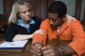 stock photo of courtroom  - Advocate and prisoner in handcuffs listening case in courtroom - JPG