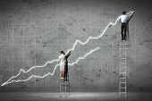 pic of climbing wall  - businesspeople standing on ladder drawing diagrams and graphs on wall - JPG
