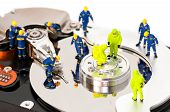 stock photo of figurines  - Group of engineers maintaining hard drive - JPG