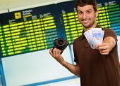 Постер, плакат: Молодой человек держа камеру и валюта евро помещении