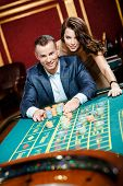 image of roulette table  - Man accompanied by woman placing bets at the roulette table - JPG