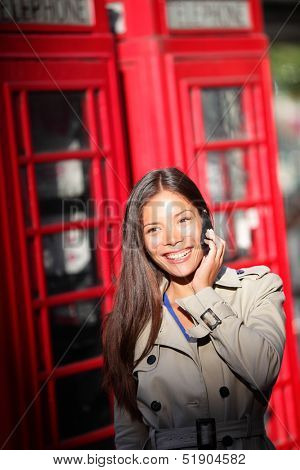 London woman taking on smartphone by red phone booth. Young casual female business woman having conversation on mobile smart phone in London, England, United Kingdom. Multiracial Asian Caucasian model