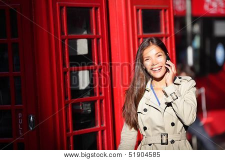 London woman taking on smart phone by red phone booth. Young casual female business woman walking with mobile phone smartphone in London, England, United Kingdom. Multiracial Asian Caucasian model.