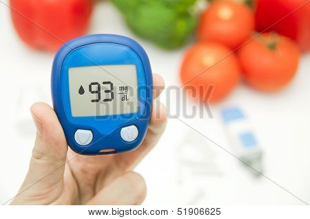 Hand holding meter. Diabetes doing glucose level test.