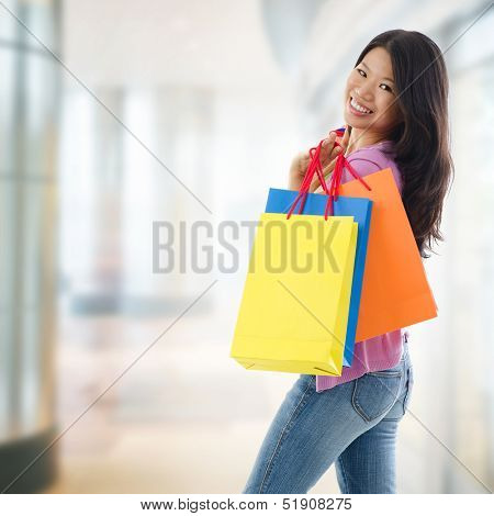 Happy Asian shopping woman smiling holding many shopping bags at the mall. Casual Asian shopper girl standing in department store. Beautiful mixed race Southeast Asian woman model.