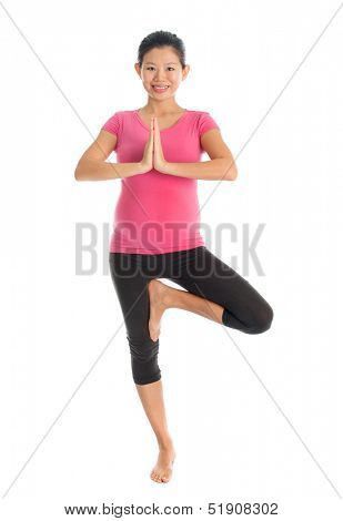 Prenatal yoga class. Full length healthy Asian pregnant woman doing yoga exercise stretching, full body isolated on white background.