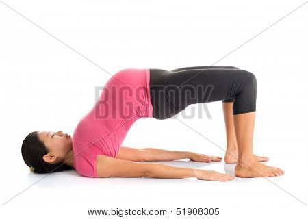Pregnancy yoga class. Full length healthy Asian pregnant woman doing yoga exercise stretching, full body isolated on white background. Yoga bridge pose.