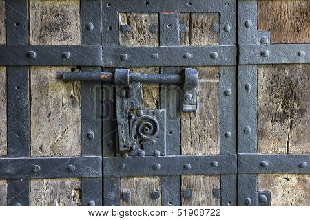 Ancient iron lock with latch on aged boarded door in Wurzburg, Germany.