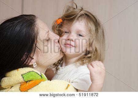 Mom hugs and kisses awakened fuzzy-looking child