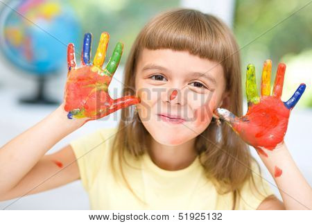 Portrait of a cute cheerful girl showing her hands painted in bright colors