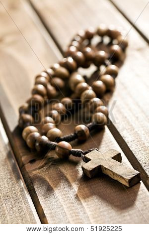 rosary beads lying on wooden background