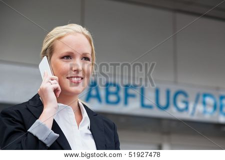 a business woman phoning with her cell phone at the airport. roaminggeb�?�??�?�?�?�¼rhen smartphones abroad