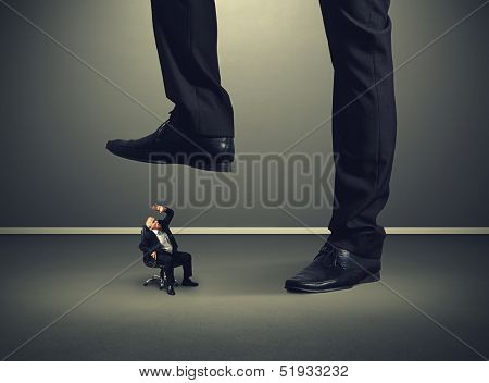 scared senior businessman under big leg his boss