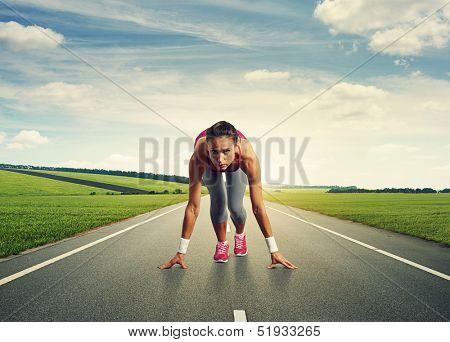 female sprinter standing on the start