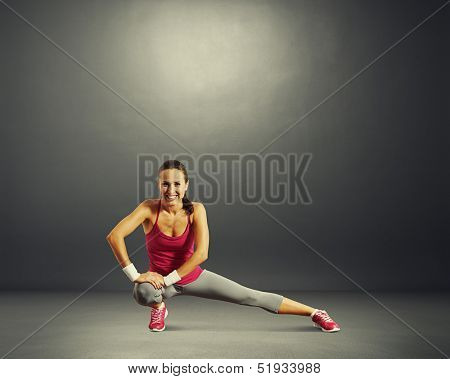 stretching sportswoman warming up over dark background