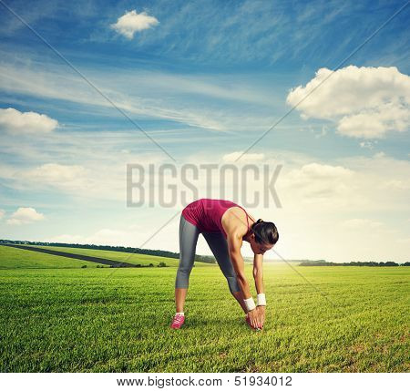 young sportswoman doing stretching exercises at outdoor
