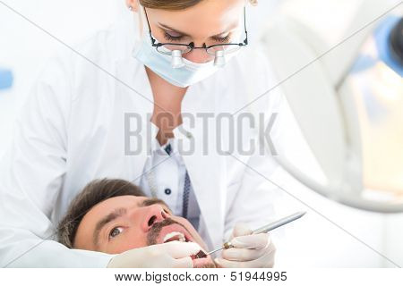Male patient with female dentist in a dental treatment, wearing masks and gloves