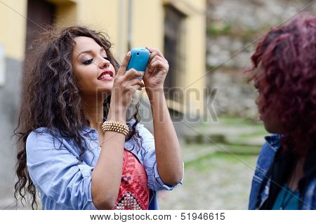 Happy Young Girls Taking Pictures Of Themselves Through Cellphone