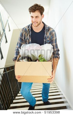 Man Moving Into New Home Carrying Box Upstairs