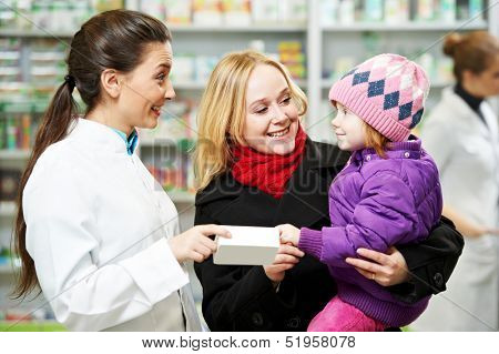 Cheerful pharmacist chemist woman demonstrating vitamins to child girl in pharmacy drugstore
