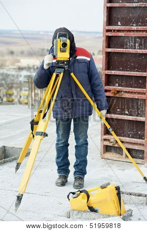 One surveyor worker working with theodolite transit equipment at construction site outdoors